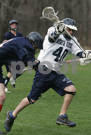 Danvers: Ben Huntley from North Shore Tech, right, maintains possession of the ball while being checked by Lynn Tech's Alex Quinton during the first period of their teams' game in Danvers on Wednesday. This season marks the first in which Tech lacrosse is competing as a varsity program. Photo by Matthew Viglianti/Staff Photographer Wednesday, April 8, 2009.