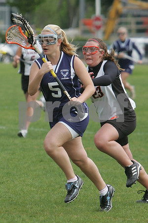 Beverly: Caroline Connors from Peabody, left, pushes the ball for the Tanners as Beverly's Ally Donnelly hustles to defend the play during their teams' game in Beverly on Monday. Photo by Matthew Viglianti/Staff Photographer Monday, May 18, 2009.