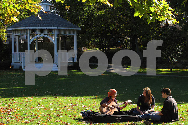 Beverly: Beverly High School students Taylor Rapalyea, center, and Brett Goodhue, listen as Flavia Kuchenny from Beverly, plays a selection of songs by Jason Mraz and Pink Floyd on her guitar on the lawn at Beverly Common on Thursday afternoon. Photo by Matthew Viglianti/Staff Photographer Thursday, October 23, 2008.