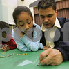Salem: Shariany Del Valle, 6, from Salem reacts as her father, Jorge, marks a square during their game of tic-tac-toe at Family Reading Night and Ice Cream Social at the Bowditch School in Salem on Tuesday. At left, Jariel Del Valle, 4, draws pictures of his friends on the paper table cloth. Photo by Matt Viglianti/Salem News Tuesday, October 14, 2008