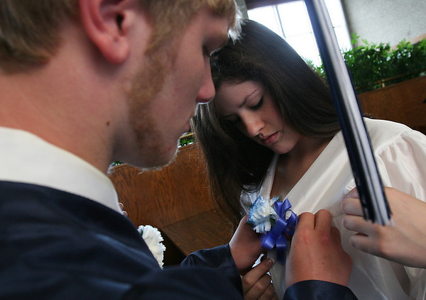 Hamilton: Scott McCulloch helps pin a flower for Kayla Barber before graduation ceremonies for the Hamilton-Wenham class of 2010 at Gordon College on Sunday. Photo by Matthew Viglianti/Staff Photographer Sunday, June 13, 2010.