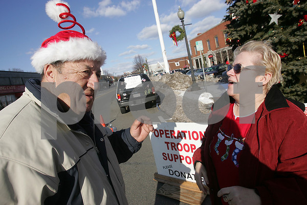 """Danvers: """"God bless him, he's out here,"""" said Jacquelyn Beeman from Danvers of Jim George, who momentarily wears a Christmas hat she gave him as he collects donations for Operation Troop Support in Danvers Sqaure on Christmas morning. George has spent the last 5 Chirstmas mornings in Danvers Square trying to raise money for the troops. Photo by Matthew Viglianti/Staff Photographer Thursday, December 25, 2008."""