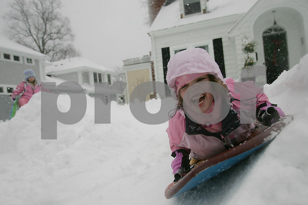 "Beverly: Emma Donoghue, 6, shrieks while sledding down a track carved by her father, William, outside their Atlantic Street home in Beverly while he sister, Keegan, 4, left, prepares to take her turn on a snowy Sunday afternoon. William referred to the sled course as ""Lake Placid,"" and said he built it for the girls while shoveling the sidewalk and driveway. Photo by Matthew Viglianti/Staff Photographer Sunday, December 21, 2008."