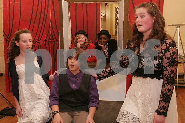 """Salem: From left Annie Tuttle, Dominic Serino, and Alex Lane, who play poets, recite their lines in unison as Kayleigh Krajeski, in red, and Mildred Aroko, the interloquters, or narrators, look on from behind a prop window during rehearsal for the Salem Academy Charter School's production of """"This is Not a Pipe Dream"""" in Old Town Hall on Wednesday. The show is a one-act play about surrealist artist Rene Magritte. Photo by Matt Viglianti/Salem News Wednesday, December 10, 2008"""