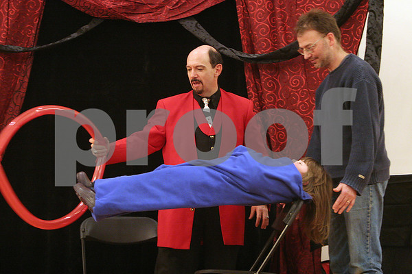 Beverly: Dan Clapp from Ipswich, right, reaches to brace his daughter, Hannah, 4, as magician Royal Sorrell uses a balloon hoop to show that there is nothing supporting Hannah's legs during a magic show at the First Baptist Church in Beverly during First Night celebrations on Wednesday. Photo by Matthew Viglianti/Staff Photographer Wednesday, December 31, 2008.