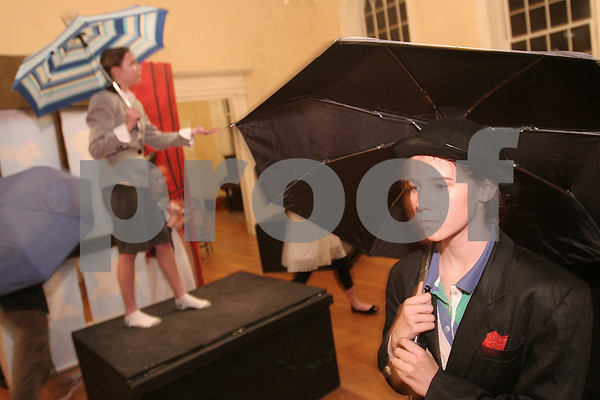 "Salem: Lydia King, right, walks through the scene with an umbrella as Jaclyn Jermyn maintains a pose on a riser during a dress rehearsal for the Salem Academy Charter School's production of ""This is Not a Pipe Dream"" at Old Town Hall in Salem on Wednesday. King plays of the the four Anonymous Men, while Jermyn plays the role of Rene Magritte, in the one-act play about the surrealist artist Magritte's life. Photo by Matt Viglianti/Salem News Wednesday, December 10, 2008"