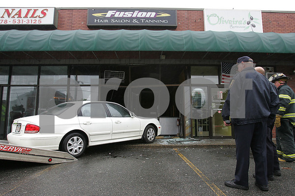 Peabody: Peabody firefighters and police officers watch as a white Hyundai Sonata is towed from inside the front entrance of Fusion Hair Salon & Tanning at 150 Main Street in Peabody on Sunday morning. The car crashed through the front window and door of the business at around 10 a.m.. Police, fire, and amublance responded to the scene. The hair salon was closed at the time of the accident, and no injuries were reported at the scene. Photo by Matthew Viglianti/Staff Photographer Sunday, June 21, 2009.