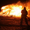 Salem: A firefighter keeps a water hose at the ready at the annual Christmas tree bonfire at Deadhorse Beach in Salem on Wednesday night. An estimated 2500 trees were burned in this year's fire. Photo by Matthew Viglianti/Staff Photographer Wednesday January 6, 2010.