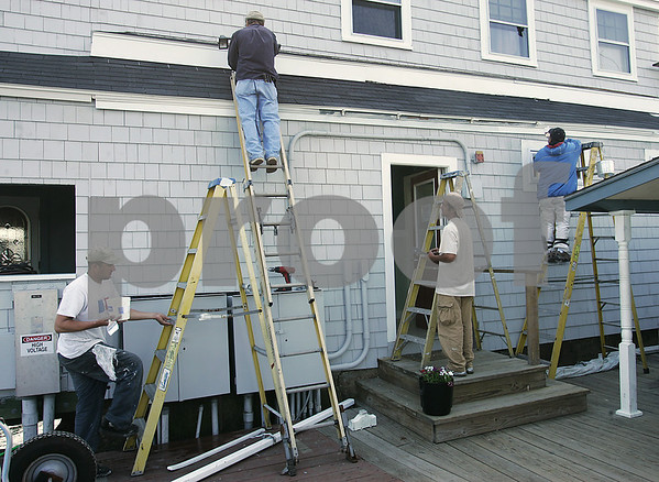 Salem: Workers put a coat of paint on a building at the Hawthorne Cove Marina in Salem in preparation for the upcoming boating season. Photo by Matthew Viglianti/Staff Photographer Wednesday, May 13, 2009.