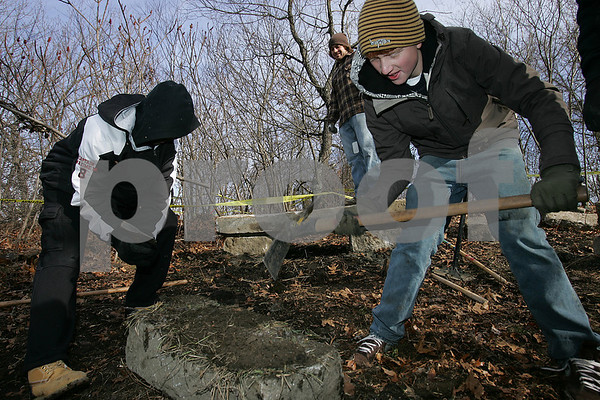 "Salem: Salem High School students, Max Mondestin, left, and Jeff Turben, work to build an outdoor, amphitheatere-style classroom on Sunday morning. Students spent the morning and afternoon preparing the area for stone benches to be moved into place, and making sure the path from the parking lot behind the field house to the site of the classroom was cleared and ready to be made wheelchair accessible for use this spring. The project, called ""Get Out and Learn,"" is being organzied by students Maggy Duffy, center in green, and Julia Gauthier, center, right. Photo by Matt Viglianti/Salem News Sunday, December 14, 2008"
