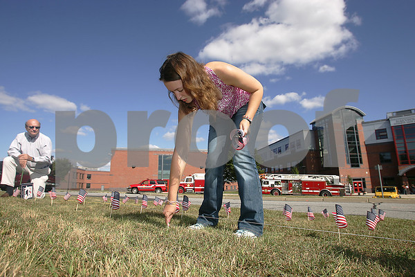 Boxford: Olivia O'Malley, a student at Masconomet High School in Boxford, places a small American flag on the lawn outside the school on Wednesday afternoon. O'Malley and several of her friends placed 3,000 flags on the lawn in memory of the vitcims of September 11, 2001. Photo by Matt Viglianti/Salem News Wednesday, September 10, 2008