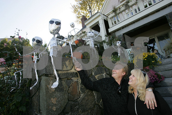 Marblehead: Alex Gediman and his wife, DD Swan Gediman shake hands with one of the 27 pipe and foil aliens decorating the front of their home on Beacon Street in Marblehead on Sunday afternoon. Photo by Matt Viglianti/Salem News Sunday, October 26, 2008