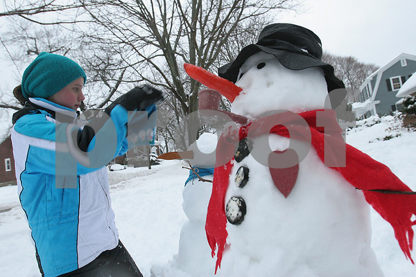 Beverly: Emma Faulkner, 10, decorates a snowman with a blue snowman hat outside her Beverly home on Wednesday afternoon. Emma spent about a half an hour making the two snowmen with her sister, Sarah, 8, enjoying their day off from school to play in the gathering snow. Emma planned to make two or three smaller snowmen to complete the snowman family. Photo by Matthew Viglianti/Staff Photographer Wednesday, January 28, 2009.
