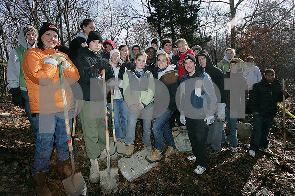 """Salem: A group of Salem High School students gather in the woods behind the school's field house to build an outdoor, amphitheatere-style classroom on Sunday morning. Students spent the morning and afternoon preparing the area for stone benches to be moved into place, and making sure the path from the parking lot behind the field house to the site of the classroom was cleared and ready to be made wheelchair accessible for use this spring. The project, called """"Get Out and Learn,"""" is being organzied by students Maggy Duffy, center in green, and Julia Gauthier, center, right. Photo by Matt Viglianti/Salem News Sunday, December 14, 2008"""