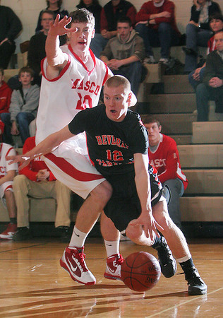 Topsfield: Mark Hannable, a senior forward for Beverly High School, right, drives past Masconomet senior captain John Daniels during the first half of their teams' game at Masconomet on Wednesday night. Photo by Matthew Viglianti/Staff Photographer Wednesday, December 30, 2009.