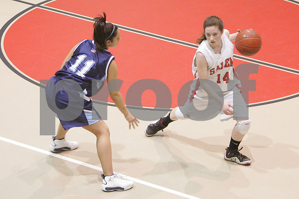 Salem: Ashley White from Salem, right, crosses over against Kenia McKeon during the third quarter of Salem's 40-28 win over Peabody in Salem on Tuesday. Photo by Matthew Viglianti/Staff Photographer Tuesday, February 3, 2009.
