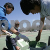 Salem: Jorge Barzola, Jr., right, and Weili Sun, both sophomore tennis players at Salem High School, help Peter Maitland of Salem mix green crack filler to fill cracks in the High School's tennis courts on Sunday afternoon. Although the tennis season has already started at Salem High, the disrepair of the courts have forced the boys and girls teams to practice at Salem Willows and Salem State. Photo by Matthew Viglianti/Staff Photographer Sunday, April 19, 2009.