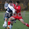 Peabody: Peabody senior Greg Doonan, left, releases a pass while being challenged by Everett's Felix Debona during the first half of the teams' Division 1 North tournament opener in Peabody on Sunday. Peabody lost 3-2 in overtime. Photo by Matthew Viglianti/Staff Photographer Sunday, November 9, 2008.