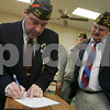 Beverly: Timothy Smith from the VFW Post 545 in Beverly, left, signs a document to change the Post's name as Brian Williams, Post Junior Vice President, right, looks on during a special meeting held on Monday night. Photo by Matt Viglianti/Salem News Monday, January 26, 2009