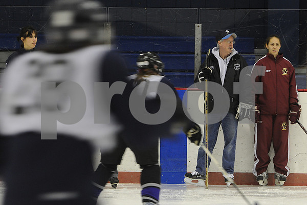 Peabody: Larry Minehan, second from right, head coach of the Peabody High School girls hockey team, watches with the rest of the coaching staff as the team warmups up with skating drills during practice on Thursday. Photo by Matthew Viglianti/Staff Photographer Thursday, December 3, 2009.