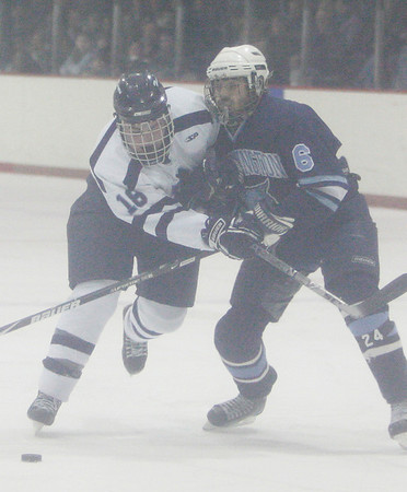 Peabody: Peabody senior Pete Sucharewicz, left, gets tangled up with Wilmington junior John Malone while on his way to the net during the second period of their teams' game in Peabody on Wednesday. Photo by Matthew Viglianti/Staff Photographer Wednesday, February 17, 2010.