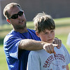 Danvers: Andrew Lucy, 13, from Danvers, listens well as Sean Rogers, the head football coach at Danvers High School, outlines a pass rushing scheme during a youth football skills clinic run by Rogers and the rest of the Falcons' football staff on Tuesday afternoon. Photo by Matthew Viglianti/Staff Photographer, Tuesday, July 27, 2010.