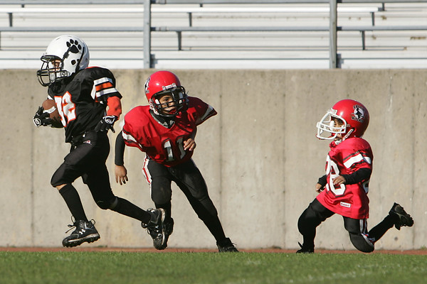 Salem: Ryan Barror from Beverly, left, streaks past the Salem defense on his way to the endzone during a youth football game at Bertram Field in Salem on Sunday. Photo by Matthew Viglianti/Staff Photographer Sunday, October 12, 2008.