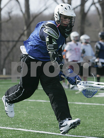 Danvers: Mitch Cunningham scoops the ball in stride during a drill at tryouts for the St. John's Prep freshmen lacrosse team on Monday afternoon in Danvers. Monday marked the start of the spring sports season for North Shore schools. Photo by Matthew Viglianti/Staff Photographer Monday, March 16, 2009.