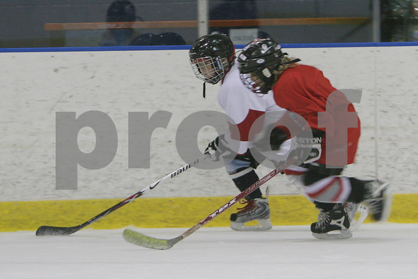 Salem: Brooke Keough, 8, from Marblehead, right, keeps paces with Kyle Fury, 8, from Marblehead, as Fury skates along the boards during a drill at practice with the Marblehead Mites 1 hockey team at Salem State on Sunday. Photo by Matt Viglianti/Salem News Sunday, January 18, 2009