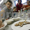 Peabody: Sarah Jaynes, 8, from Peabody, right, paints an online on her gingerbread man as Daniel Smith, 10, from Peabody, reaches to grab a piece of candy to decorate his cookie during a program called Kids in the Kitchen at the Center School in Peabody on Monday. The class is grant funded and is run by parent Sandi Dover. The kids meet once a week to learn about nutritious meals and snacks. Photo by Matt Viglianti/Salem News Monday, December 22, 2008