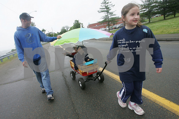 Salem: Jake Lukk, 5, from Plymouth, second left, and his cousin Nicky Copp, 5, from Salem, second right, catch a ride down Memorial Drive in Salem in a wagon pulled by Nicky's sister Kali, 7, as Sven Lukk, Jake's father, walks beside his son and nephew during the 2009 North Shore Medical Center Cancer Walk on Sunday. Photo by Matthew Viglianti/Staff Photographer Sunday, June 21, 2009.