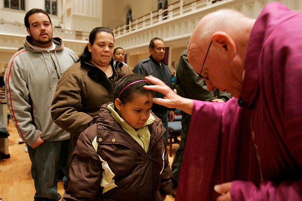 Salem: Rev. Charles Bourque bends to paint a cross of ash on the forehead of Jaelin Arroyo of Salem, 6, as Arroyo's grandmother Crispina Arroyo and cousin Justin Corchado wait in line behind her during an evening service at Immaculate Conception Parish in Salem on Ash Wednesday. Photo by Matthew Viglianti/Staff Photographer Wednesday, February 17, 2010.