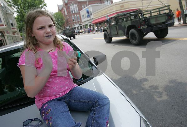 Beverly: With her lips blue from a lollipop, Cassy Garboski, 7, watches and claps from the hood of her grandmother's car as military vehicles drive down Cabot Street during the Beverly Memorial Day Parade on Sunday afternoon. Photo by Matthew Viglianti/Staff Photographer Sunday, May 24, 2009.