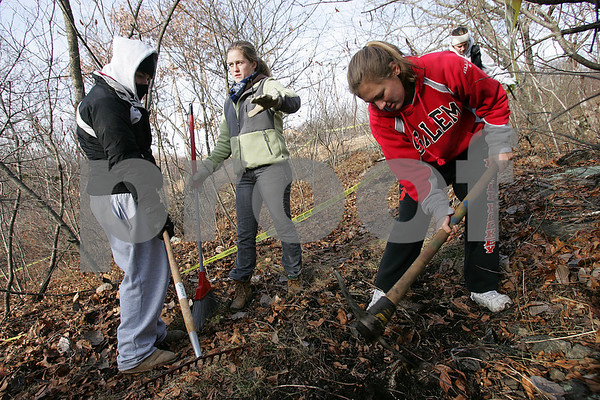 Salem: Maggy Duffy, center, speaks with Madeleine Lutts, left, as Jillian Robinson uses a pick ax to clear debris from a trail leading to an outdoor, amphitheatere-style classroom Duffy is helping to organzie outside of Salem High School on Sunday. Students from the high school spent the morning and afternoon preparing the area for stone benches to be moved into place, and making sure the path from the parking lot behind the field house to the site of the classroom was cleared and ready to be made wheelchair accessible for use this spring. Photo by Matt Viglianti/Salem News Sunday, December 14, 2008