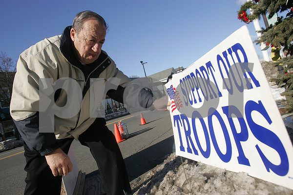 "Danvers: Jim George uses tape to secure a sign asking for donations to Operation Troop Support in Danvers Square on Christmas morning. For George, Thursday marked his fifth straight Christmas morning raising money for Operation Troop Support in Danvers. ""That's the sign I want people to see right there,"" he said of a sign reading ""Pray for our troops,"" taped to the rear windshield of his SUV. Photo by Matthew Viglianti/Staff Photographer Thursday, December 25, 2008."