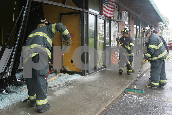 Peabody: Peabody firefighters clear debris at the scene of an accident at 150 Main Street in Peabody, where a white Hyundai Sonata drove over the curb an through the front window and door of Fusion Hair Salon & Tanning at around 10 a.m. on Sunday. Police, fire, and amublance responded to the scene. The hair salon was closed at the time of the accident, and no injuries were reported at the scene. Photo by Matthew Viglianti/Staff Photographer Sunday, June 21, 2009.