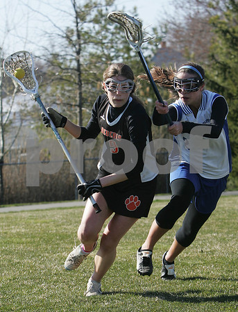 Danvers: Beverly senior Erin Bushey, left, tries to break free from Danvers senior Erica Veilleux during their teams' game in Danvers on Thursday afternoon. Photo by Matthew Viglianti/Staff Photographer Thursday, April 16, 2009.