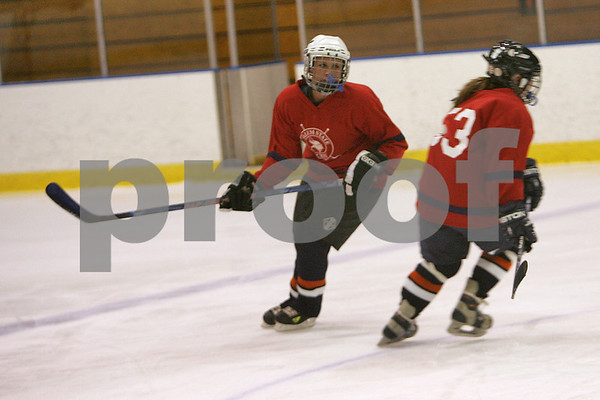 Salem: Taylor Orlando, left, and Katie LaPrad cross paths during a skating drill with the Endicott College and Salem State women's club hockey team in Salem on Wednesday. Photo by Matthew Viglianti