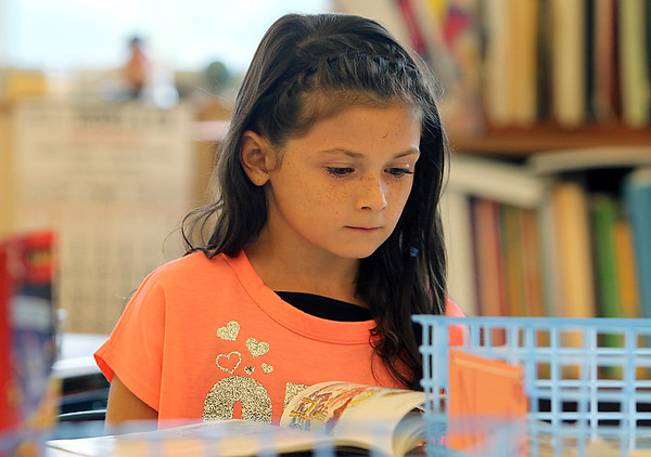 Brown School third grader Nicole Panzini, reads a book on the first day of school on Tuesday afternoon. David Le/Staff Photo