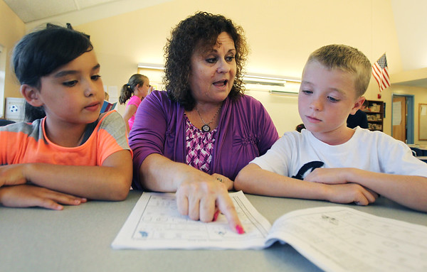Brown School Principal Elaine Metropolis, center, sits with fourth graders Cade Buckley, right, and Olivia Garvey, left, and reviews a summer math book on the first day of school for the City of Peabody. David Le/Staff Photo