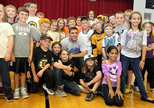 Boston Bruins forward Milan Lucic, center, poses for a photo with the 4th graders at Riverside Elementary School in Danvers on Thursday afternoon. David Le/Staff Photo