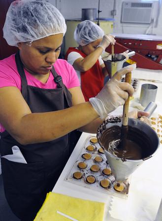 Salem:<br /> Isabelle Suriel, left, and Isabelle Fernandez make candy sand dollars at Harbor Sweets.<br /> Photo by Ken Yuszkus, The Salem News, Thursday, September 19, 2013.