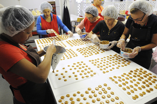Salem:<br /> Griselda Encarnacion, left, quickly pours caramel dollops onto sheets as other workers add pecans before the caramel cools at Harbor Sweets. They are making candy sand dollars.<br /> Photo by Ken Yuszkus, The Salem News, Thursday, September 19, 2013.