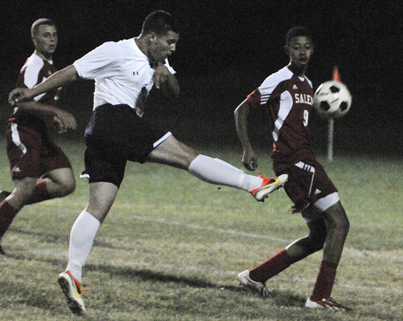 Peabody:<br /> Peabody's Jake Silva kicks the ball with Salem's Alejandro Smart at his side during the Salem at Peabody boys soccer game.<br /> Photo by Ken Yuszkus, The Salem News, Monday, September 23, 2013.