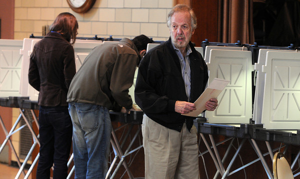 Salem:<br /> Jim Kilroy, right, just finished marking his ballot at the St. John's Church polling location. In the background voting are Karen Cummings and Mike Mangini.<br /> Photo by Ken Yuszkus, The Salem News, Tuesday, September 17, 2013.
