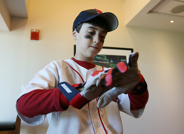 Boston: Gloucester native Jacoby Catanzaro, 9, tries on game worn batting gloves given to him by his favorite player, Boston Red Sox center fielder Jacoby Ellsbury, on Sunday afternoon. David Le/Salem News