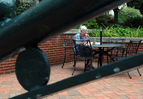 Beverly:<br /> Beverly Public Library childrens room assistant Pat Danielson reads while eating her lunch in the courtyard of the library just before the rain arrived on Tuesday.<br /> Photo by Ken Yuszkus, The Salem News, Tuesday, September 10, 2013.