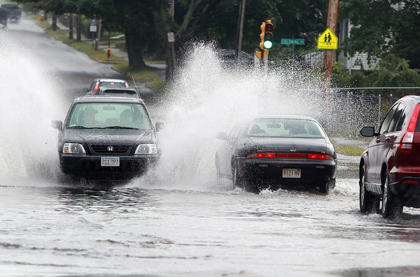 Peabody: Cars along Margin St. in Peabody splash through a deep puddle caused by a short downpour on Monday afternoon. David Le/Salem News