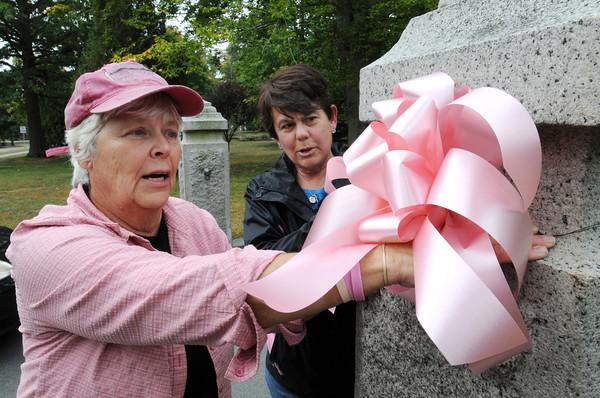 """Danvers:<br /> Elaine """"Ham"""" Glass, left, and  Elaine Seifert attach pink bows to the pillars at the Peabody Institute Library as part of their  pink up Danversfor breast cancer awareness campaign.<br /> Photo by Ken Yuszkus, The Salem News, Monday, September 30, 2013."""