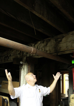 Ipswich: Fire Chief Rick Smith gestures towards the basement ceiling where there are visible water stains on the wood beams, to where their trucks are kept up above. David Le/Salem News
